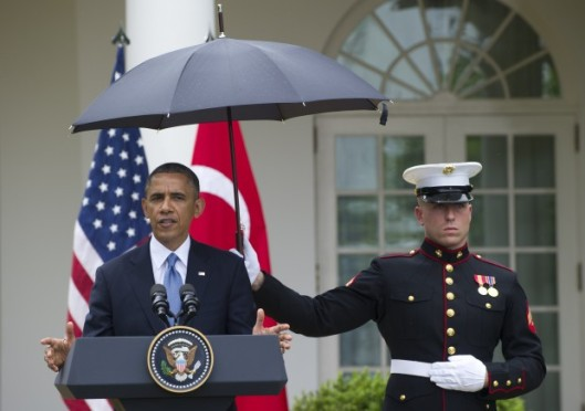 A US Marine holds an umbrella for US President Barack Obama during a brief rain shower as he hold a joint press conference with Turkish Prime Minister Recep Erdogan in the Rose Garden of the White House in Washington, DC, May 16, 2013. (Photo: SAUL LOEB/AFP/Getty Images)