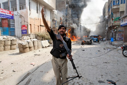A Pakistani police officer calls for help moments after a car bomb attack in Peshawar, Pakistan, Sunday, Sept. 29, 2013. (AP Photo/Mohammad Sajjad)